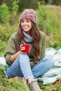 Smiling young woman with cup sitting in camping Stock Photos