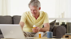 Senior man checking laptop for digital prescription - stock footage