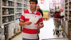 Man with trolley checking shopping list at supermarket. HD. 1920x1080 Stock Footage