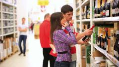 Young family couple choosing bottle of wine in supermarket during weekly Stock Footage