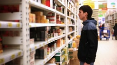 Young man is shopping in supermarket. Choosing tea In the shop. HD. 1920x1080 Stock Footage