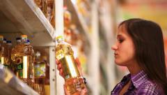 Young woman buys sunflower oil in supermarket. HD. 1920x1080 Stock Footage