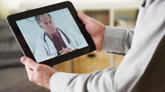 Senior patient talking to tablet doctor Stock Footage
