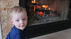 A toddler by a fire in the living room dolly Stock Footage