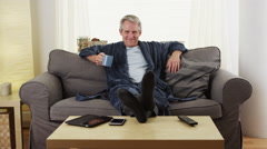 Senior man sitting couch with coffee Stock Footage