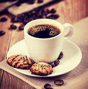 Cup of coffee and cookies on the table. Vintage retro hipster style version - stock photo