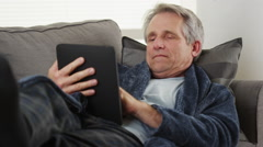 Elderly man falls asleep with tablet Stock Footage