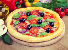 Tasty pizza and fresh ingredients on the table Stock Photos
