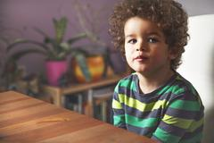 Cute young boy sitting on chair, at home. - stock photo