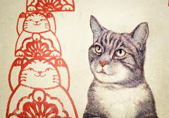 Penang mural with realistic picture of a tortoiseshell cat beside red, stylized  - stock photo