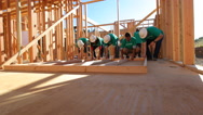 Stock Video Footage of Volunteers working together lifting wall