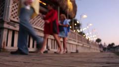 People walking along bar deck on beach Stock Footage