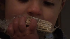 Stock Video Footage of Hungry child eats a pack of crackers unpacked zoom out