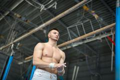 Athlete topless preparing to give gymnastic exercises on the une - stock photo