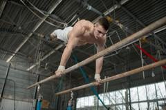 Athlete topless doing exercises on the uneven bars - stock photo
