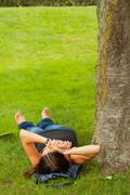 Female relaxing on the lawn in the park. - stock photo