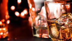 Close-up pouring whiskey on bar table near bottles warm atmosphere Stock Footage