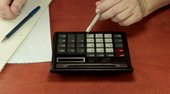 Left hand is pushing calculator buttons with pencil eraser Stock Footage