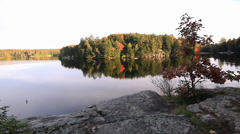Fall colors reflections on tranquil lake in Ontario cottage country Stock Footage