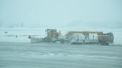 Snowplow cleaning airport runway during snow storm Stock Footage