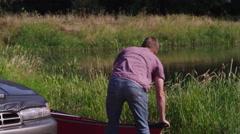 Family unloading canoe off car - stock footage