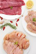 Plates with raw meat on a white table Stock Photos