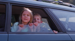 Two children looking out car window - stock footage