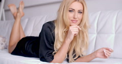 Seductive Woman in Black Robe Lying on Sofa Stock Footage