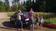 Family unloading car at camp site - stock footage