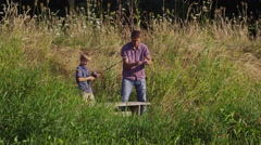 Father and son fishing at lake - stock footage