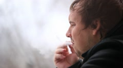 Man smoking cigarette and looking in the window. He coughs but continues to Stock Footage