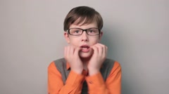 Boy hands to his mouth fright shock glasses ten years on a gray background Stock Footage