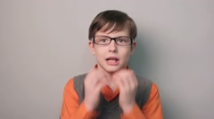 Boy hands to his mouth fright shock glasses ten years on gray background Stock Footage