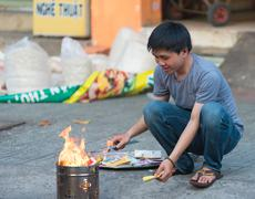 Vietnamese man burns votive offerings Stock Photos