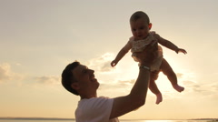 Stock Video Footage of Happy Father Holding Up Cute Baby In Air, Sunset Sky Silhouette HD