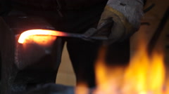 Smith forges a horseshoe on an anvil in a smithy Stock Footage