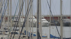 Barcelona Harbour - telephoto through yacht masts onto luxury yachts Stock Footage