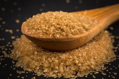Brown sugar in wooden spoon on dark background Stock Photos
