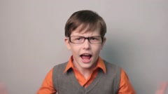 Teenager boy swears row waving his arms opened his mouth in glasses on gray Stock Footage