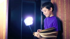 Teenager boy child reads book, standing against the wall in apartment page Stock Footage