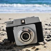 old camera on the beach - stock photo