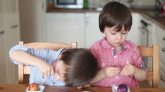 Two adorable boys, coloring eggs for Easter at home, having fun Stock Footage