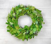 Seasonal green leaf wreath on rustic white wood Stock Photos