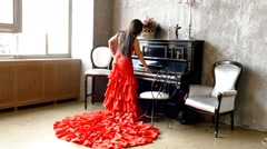 Beautiful young attractive woman in evening dress with piano Stock Footage