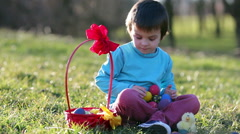 Cute boy in the park, having fun with colored eggs for Easter, springtime Stock Footage