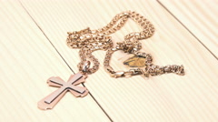 Woman Takes a Golden Cross with a Chain on the Wooden Table. 4K Stock Footage
