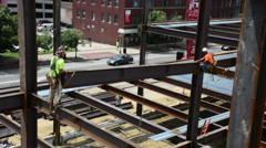 Steelworkers construct a 12-story commercial building - stock footage