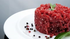 Big raw hamburger cutlet with sprouts and chilli pepper over bla Stock Footage