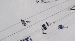 Directly above shot of people skiing below ski lift - stock footage