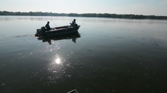 Two men on a small fishing boat cruise out to fish Stock Footage
